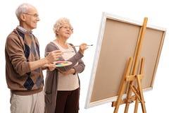 Ältere Mann- und Frauenmalerei auf einem Segeltuch mit Malerpinseln Lizenzfreie Stockbilder