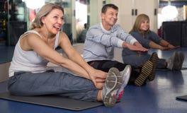 Ältere Menschen, die Übung auf Matte in der modernen Turnhalle tun stockfotos