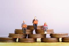 Ältere Menschen, die auf Münzenstapel sitzen Ruhestandsvorsorge stockbilder