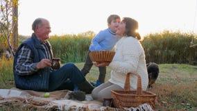 Ältere Menschen mit Kind und Haustier sitzen auf Picknickstoff mit Korb auf Hintergrund der Natur stock video footage