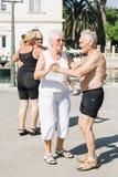 Ältere Menschen tanzen und genießen das Leben draußen auf der Ufergegend der Insel Stockbild