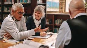 Ältere Mitschüler, die eine Diskussion sitzt in einer Bibliothek haben stockbild
