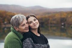 Ältere Mutter, die ihre erwachsene Tochter nahe See umarmt Lizenzfreies Stockbild
