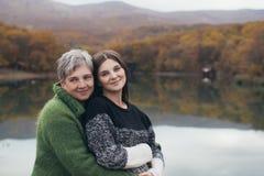 Ältere Mutter, die ihre erwachsene Tochter nahe See umarmt Stockbild