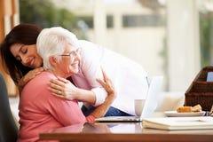 Ältere Mutter, die von der erwachsenen Tochter getröstet wird Stockbilder