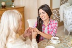 Ältere Mutter und ihr Tochterhändchenhalten beim Sitzen am Tisch lizenzfreies stockfoto