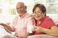 Ältere Paar-Lesezeitung zu Hause stockfotos