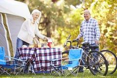 Ältere Paar-Reitfahrräder an kampierendem Feiertag Stockfoto