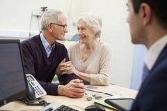 Ältere Paar-Sitzung mit Berater In Hospital Stockfotografie