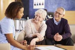 Ältere Paar-Sitzung mit Krankenschwester In Hospital Stockbild