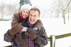 Ältere Paar-stehende Außenseite in der Snowy-Landschaft Stockfotos
