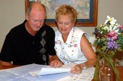 Ältere Paarbetrachtungs-Hauspläne Lizenzfreies Stockfoto