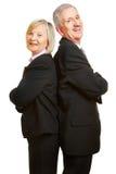 Ältere Paare als Wirtschaftler, die zurück zu Rückseite sich lehnen Stockbild