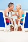 Ältere Paare auf dem Strand, der in den Stühlen trinken Champagne sich entspannt Lizenzfreie Stockfotografie