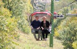 Ältere Paare auf einer Sesselbahn, die Landschaft genießt Stockfotografie