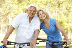 Ältere Paare auf Schleife-Fahrt im Park lizenzfreies stockfoto