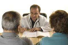 Ältere Paare an der Abfrage des Doktors Stockfotos