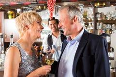 Ältere Paare an der Bar mit Glas Wein in der Hand Stockfoto