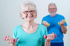 Ältere Paare in der Eignungs-Klasse unter Verwendung der Gewichte lizenzfreie stockfotografie