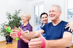 Ältere Paare der physiologischen Vertretung, wie man Gummiband als Expander benutzt Lizenzfreie Stockbilder