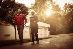 Ältere Paare in der Sportkleidung, die zusammen auf Roa läuft stockfoto