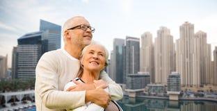 Ältere Paare, die über Dubai-Stadtufergegend umarmen stockbilder