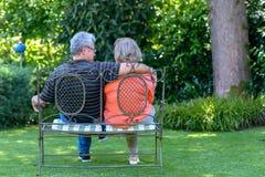Ältere Paare, die auf Bank im Garten sitzen Stockfotos