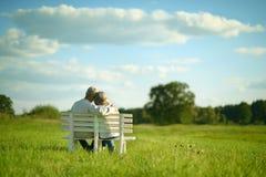 Ältere Paare, die auf Bank sitzen Lizenzfreies Stockbild