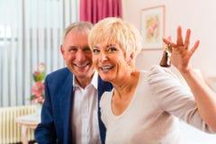Ältere Paare, die auf Bett im Hotelzimmer sitzen Lizenzfreies Stockbild