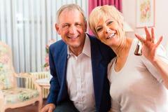 Ältere Paare, die auf Bett im Hotelzimmer sitzen Stockfoto