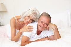 Ältere Paare, die auf Bett sich entspannen stockfotografie
