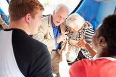 Ältere Paare, die auf Busfahrt bedrängt werden Lizenzfreies Stockfoto
