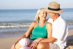 Ältere Paare, die auf dem entspannenden Strand sitzen lizenzfreies stockfoto