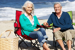 Ältere Paare, die auf dem Strand hat Picknick sitzen Stockbilder