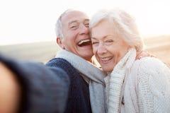 Ältere Paare, die auf dem Strand nimmt Selfie stehen Stockfoto