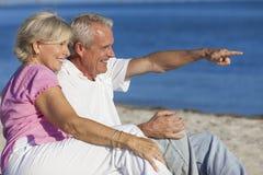Ältere Paare, die auf dem Strand-Zeigen sitzen Stockbild