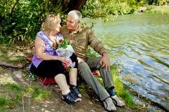 Ältere Paare, die auf den Ufern sitzen lizenzfreie stockbilder