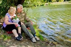 Ältere Paare, die auf den Ufern sitzen lizenzfreies stockbild