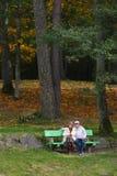 Ältere Paare, die auf einer Bank sitzen lizenzfreie stockfotos