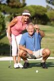 Ältere Paare, die auf Golfplatz Golf spielen lizenzfreie stockfotos
