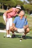 Ältere Paare, die auf Golfplatz Golf spielen lizenzfreie stockbilder