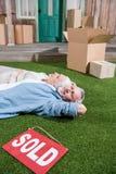 Ältere Paare, die auf grünem Gras zwischen Pappschachteln und Verkaufszeichen liegen Lizenzfreies Stockfoto
