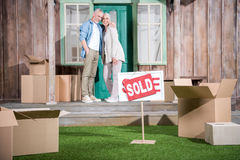 Ältere Paare, die auf Portal des neuen Hauses stehen und Verkaufszeichen auf grünem Gras Stockfotografie