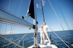 Ältere Paare, die auf Segelboot oder -yacht im Meer umarmen Stockbilder