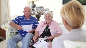 Ältere Paare, die auf Sofa Talking To Financial Advisor sitzen stock footage