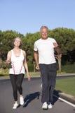 Ältere Paare, die auf Straße laufen stockbild