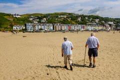 Ältere Paare, die auf Strand gehen Stockfotografie