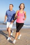 Ältere Paare, die auf Strand trainieren Lizenzfreies Stockfoto