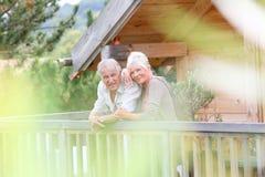 Ältere Paare, die auf Terrasse auf holdays stehen Lizenzfreie Stockbilder