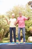 Ältere Paare, die auf Trampoline im Garten springen Stockfoto